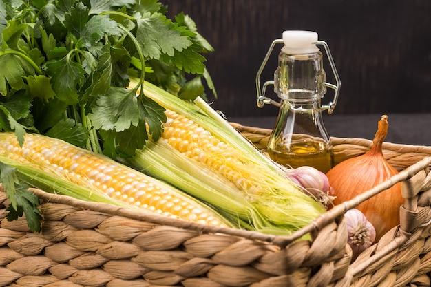 Espigas de milho frescas, salsa verde, óleo na garrafa e alho na cesta de vime. fechar-se. fundo preto.