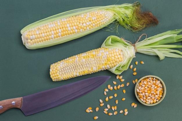 Espigas de milho fresco com grãos cortados. a faca encontra-se na mesa. espiga de milho com folhas. grãos de milho na mesa. fundo verde. postura plana