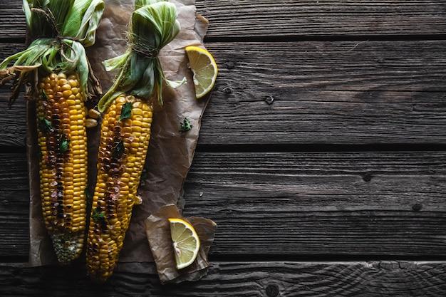 Espigas de milho grelhadas com molho de coentro em um antigo fundo de madeira comida mexicana
