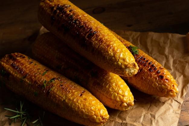 Espigas de milho grelhadas no fundo de madeira.