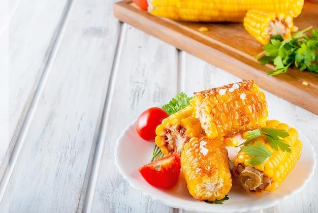 Espigas de milho grelhado com solt, especiarias e tomates