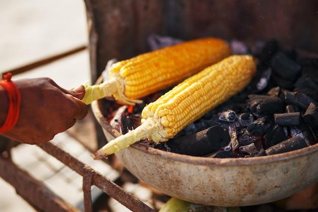 Espigas de milho na grelha. feche acima da imagem com grãos e mãos. comida de rua asiática, indiana e chinesa. praia de comida no pôr do sol do goa