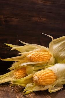 Espigas de milho na tabela de madeira do vitage.
