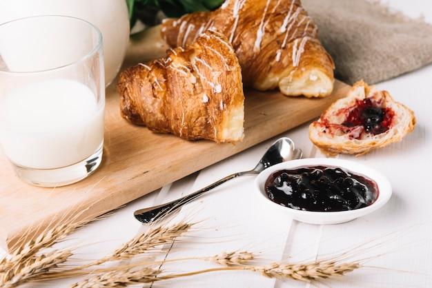 Espigas de trigo, copo de leite e geléia de frutas com croissant na mesa