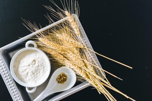 Espigas de trigo e farinha em fundo preto