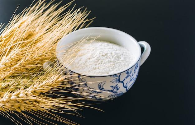 Espigas de trigo e farinha no preto