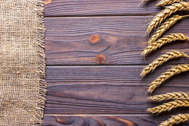 Espigas de trigo e pano em fundo de madeira