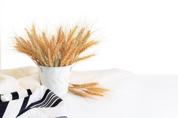 Espigas de trigo em um balde, talit em uma mesa de madeira