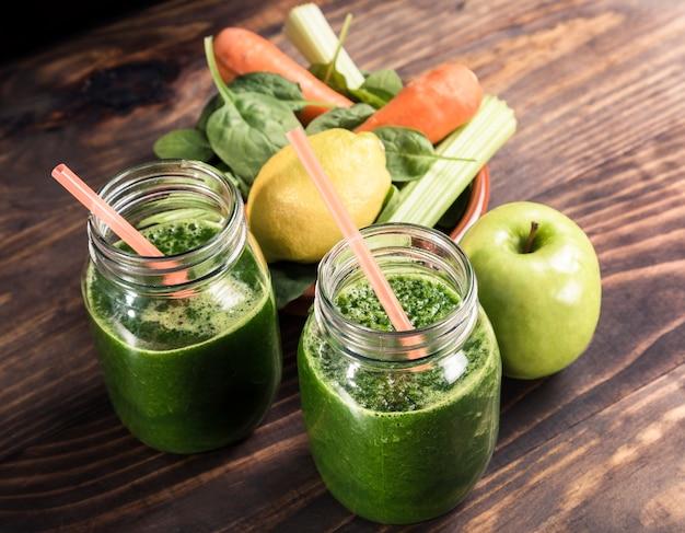 Espinafre com suco de maçã e vegetais uma jarra de refrigerante com canudo na mesa de madeira