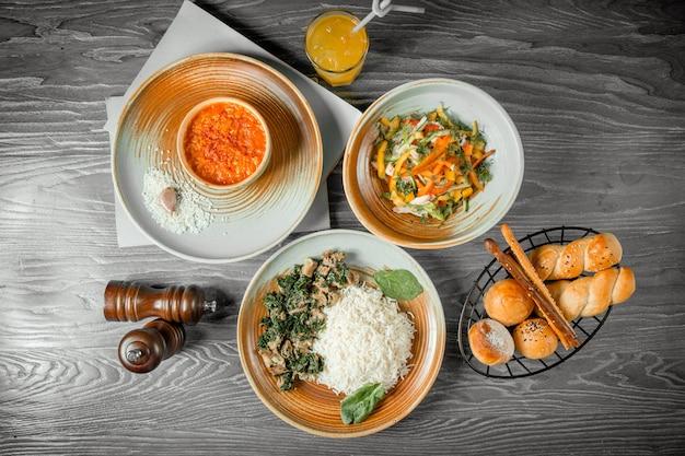 Espinafre de frango de almoço de negócios com sopa de arroz salada de frango pão bebida e pimenta preta na mesa