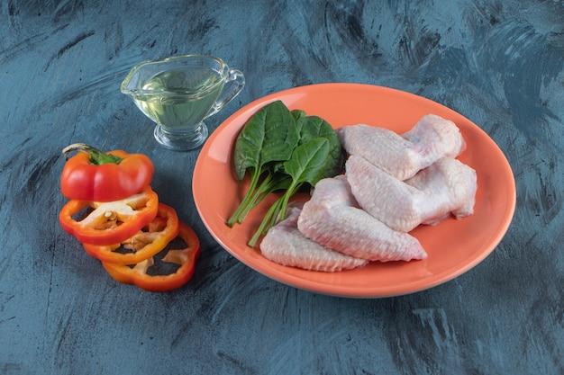 Espinafre e asa de frango em um prato ao lado de pimenta fatiada e uma tigela de óleo, na superfície azul.