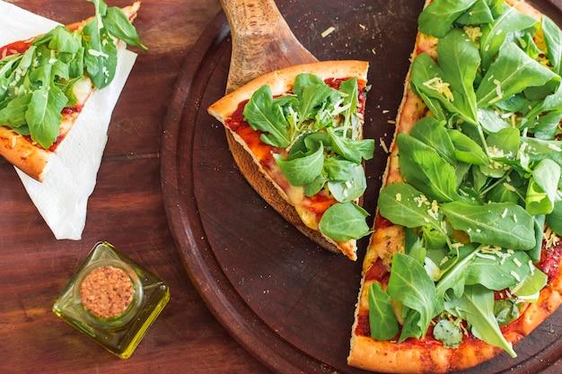 Espinafre na fatia de pizza sobre a bandeja circular de madeira