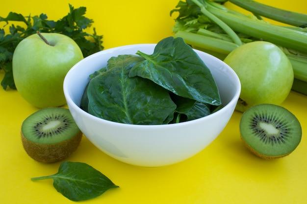 Espinafre na tigela branca e frutas verdes