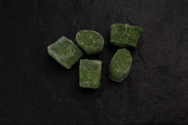 Espinafre verde esmagado congelado em forma de briquetes em pedra escura texturizada
