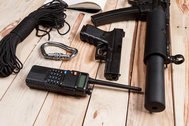 Espingarda de assalto, arma, faca com bainha, bússola e notebook com caneta na mesa.