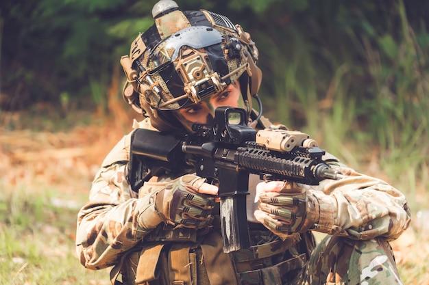 Espingarda de assalto do soldado das forças especiais com silenciador. atirador na floresta.