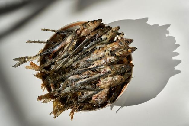 Espinhas e cabeças de peixe que sobraram depois de comer em um prato. frigideira de peixe frito em um fundo claro. esqueletos de peixe