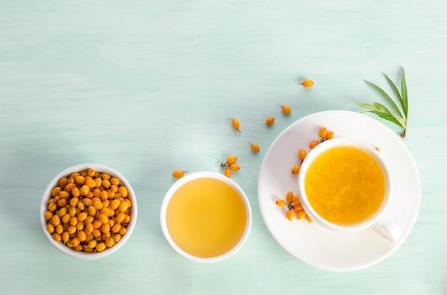 Espinheiro-mar em uma tigela de porcelana, mel e xícara de chá