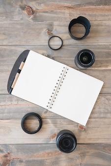 Espiral em branco abriu o livro; lentes da câmera; anéis de caneta e extensão na mesa de madeira