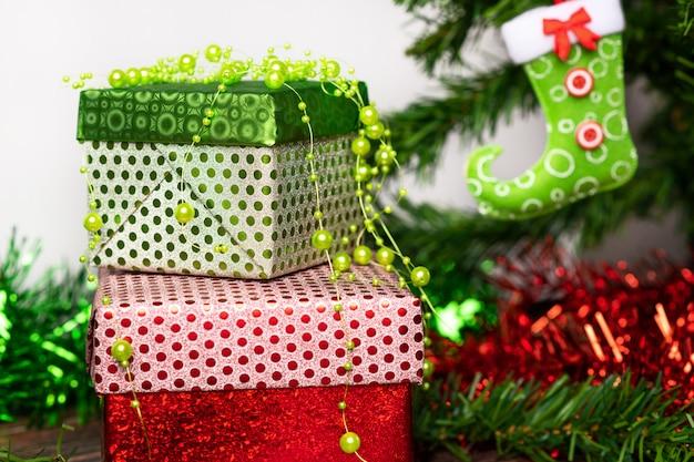 Espirito natalino. um par de presentes embalados em uma brilhante embalagem festiva, ao lado da qual um pirulito brilhante em forma de bengala, localizado em uma mesa de madeira ao lado da árvore de natal. fechar-se.
