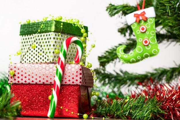 Espirito natalino. um par de presentes embalados em uma brilhante embalagem festiva, ao lado da qual um pirulito brilhante em forma de bengala, localizado em uma mesa de madeira ao lado da árvore de natal.