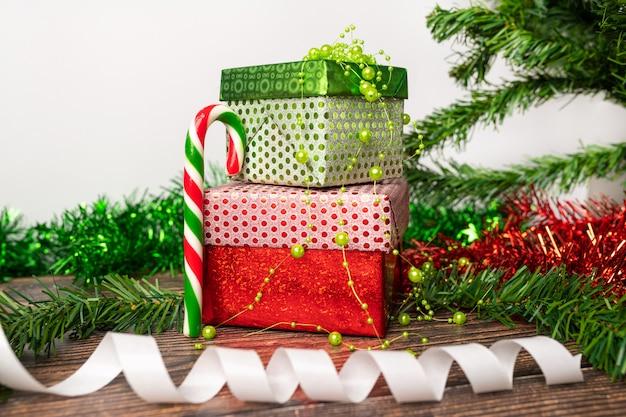 Espirito natalino. um par de presentes embalados em uma brilhante embalagem festiva, na qual são contas verdes para decoração, há um pirulito colorido na forma de uma bengala e uma fita branca de presente.