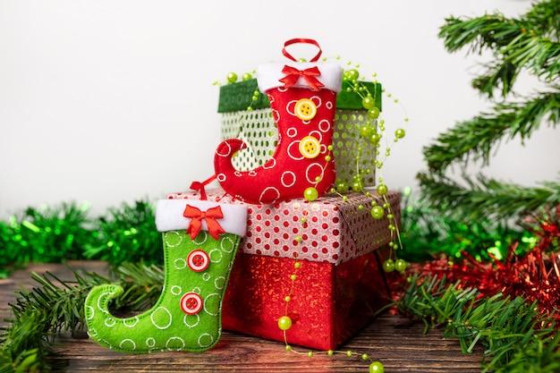 Espirito natalino. um par de presentes embalados em uma embalagem festiva brilhante, na qual estão localizadas meias brilhantes para doces. acessórios. o feriado chega até nós.
