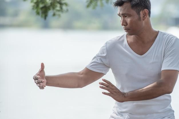Espiritual do homem mãos fazendo tai chi ou tai ji, artes marciais de chinês tradicional.