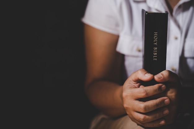 Espiritualidade e religião, as mãos postas em oração sobre uma bíblia sagrada na igreja conceito de fé.