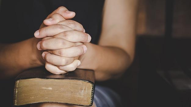 Espiritualidade e religião, as mãos postas em oração sobre uma bíblia sagrada na igreja