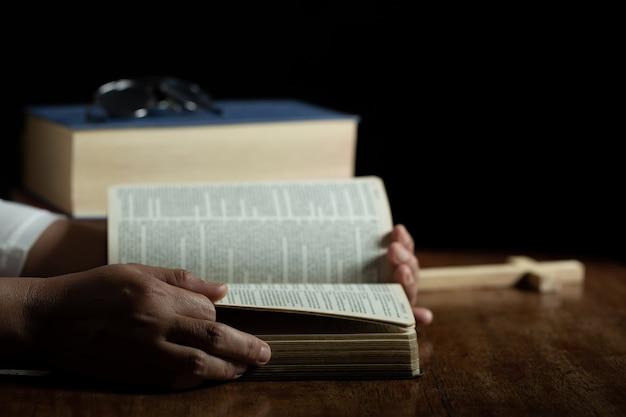 Espiritualidade e religião, mãos cruzadas em oração em uma bíblia sagrada na igreja