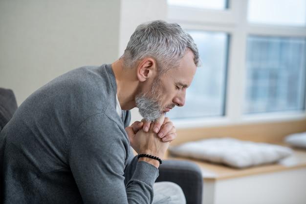Espiritualidade. um homem de cabelos grisalhos sentado com os olhos fechados e dizendo os pagadores