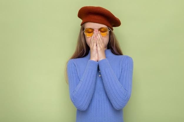 Espirros agarrados pelo nariz linda garotinha usando chapéu com óculos isolado na parede verde oliva
