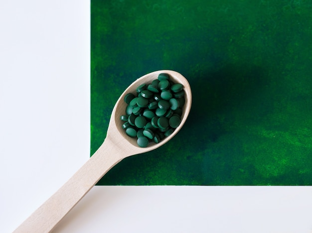 Espirulina havaiana verde em colheres de sopa, comprimidos, colher de pau, sobre fundo verde com vela