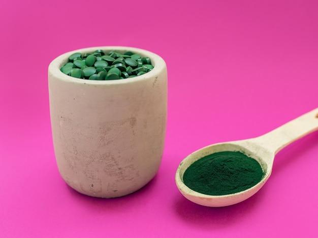 Espirulina havaiana verde em colheres de sopa, pílulas e pó em fundo rosa