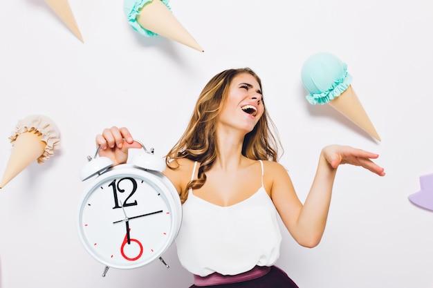 Esplêndida jovem em um top branco posando com os olhos fechados, segurando o relógio na parede decorada. retrato de menina morena animada rindo em frente a parede com doces de brinquedo nele.