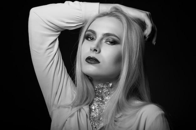Esplêndida modelo loira posando no estúdio com maquiagem brilhante e papel alumínio no pescoço. foto monocromática