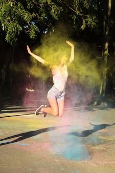 Esplêndida mulher morena pulando com pó de holi rosa, azul e amarelo explosivo no parque