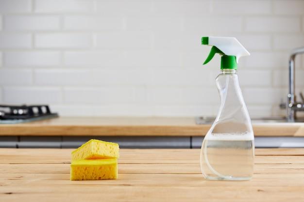 Esponja amarela e garrafa de plástico com líquido na mesa de madeira, fundo da cozinha
