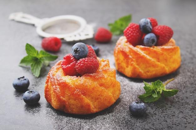 Esponja bolos com framboesas e mirtilos em uma prancha de madeira