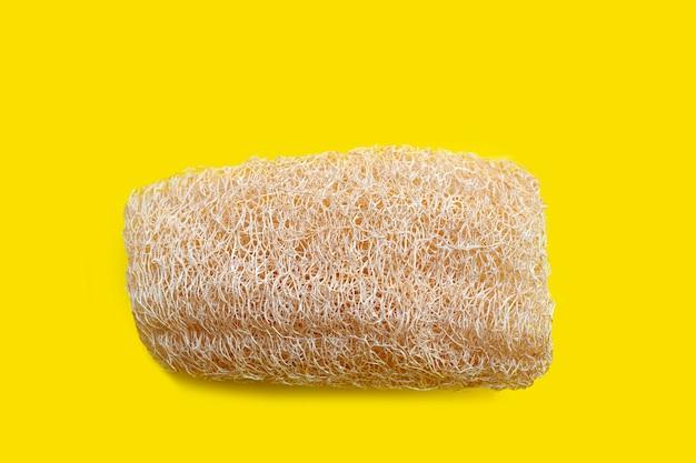 Esponja cabaça para banho em fundo amarelo.