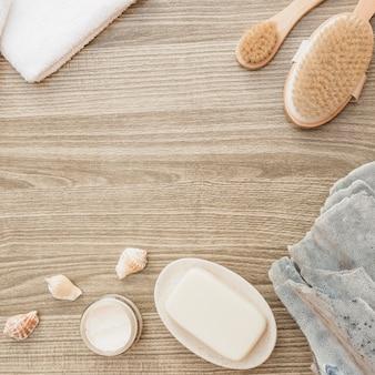Esponja; concha do mar; sabonete; escova; toalha e creme hidratante na superfície de madeira