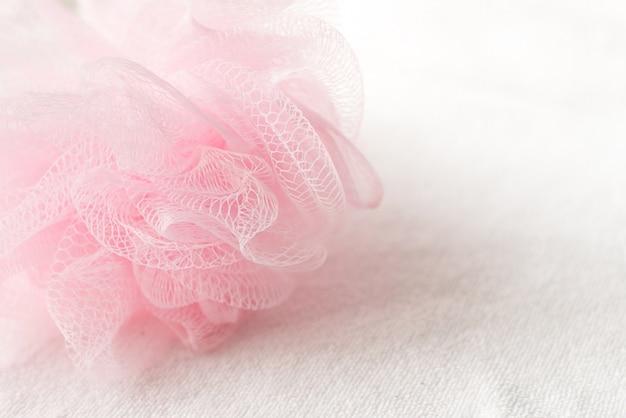 Esponja cor-de-rosa do chuveiro da malha no fundo branco.
