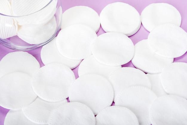 Esponja de algodão em um fundo rosa com um frasco de vidro