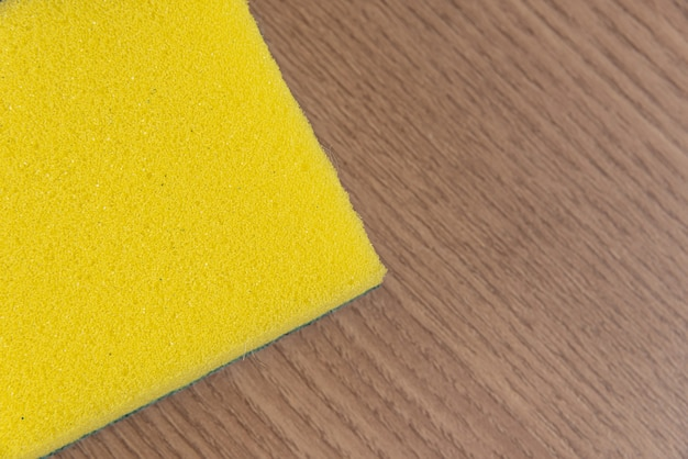 Esponja de cozinha na mesa de madeira