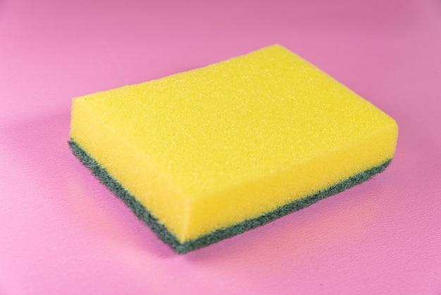 Esponja de cozinha na superfície rosa
