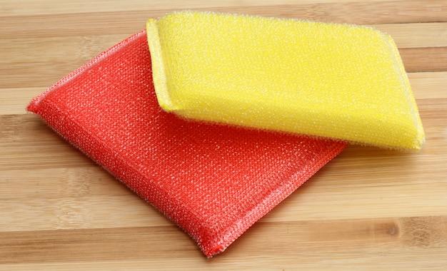 Esponja de lavar louça, pano de prato e esfregão em fundo de madeira