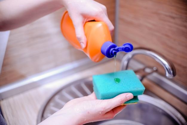 Esponja de prato com sabão de lavar louça. conceito de limpeza da casa.