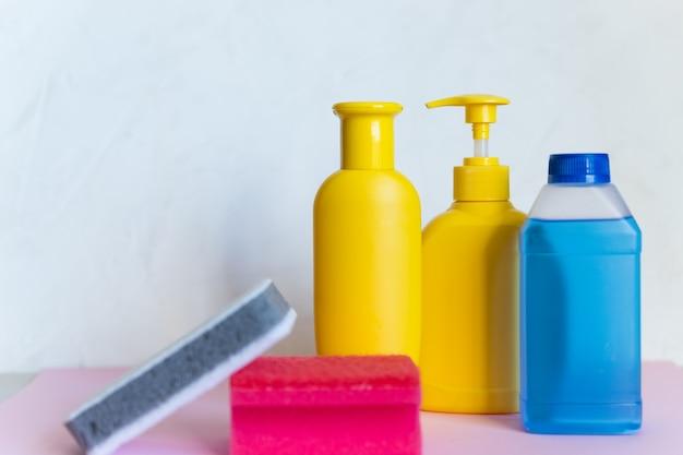 Esponja e garrafas plásticas com produtos de limpeza