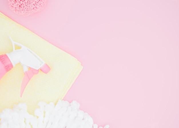 Esponja; frasco de spray e guardanapo no pano de fundo rosa